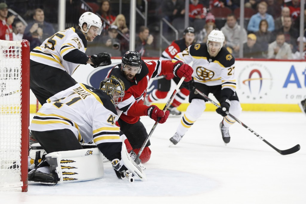 New Jersey Devils right wing Kyle Palmieri (21) tries to force the puck in as Boston Bruins goaltender Jaroslav Halak (41) defends during the second p...