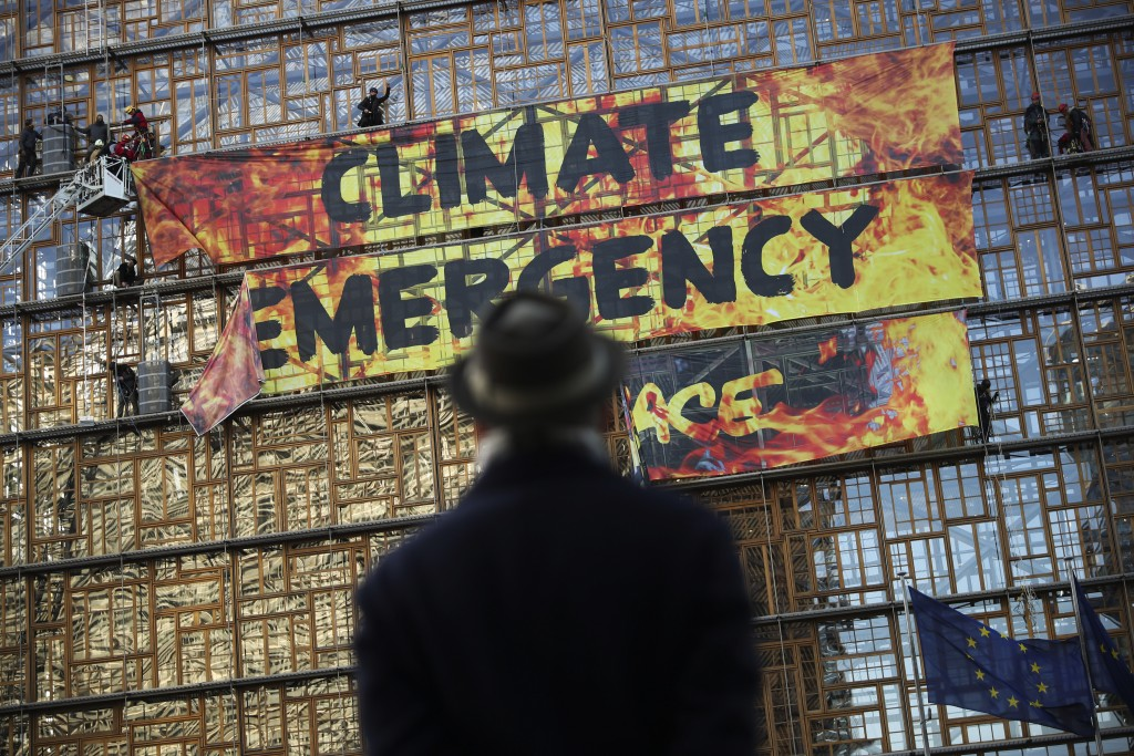 FILE - In this file photo dated Thursday, Dec. 12, 2019, a man looks up as police and fire personnel move in to remove climate activists and their ban...