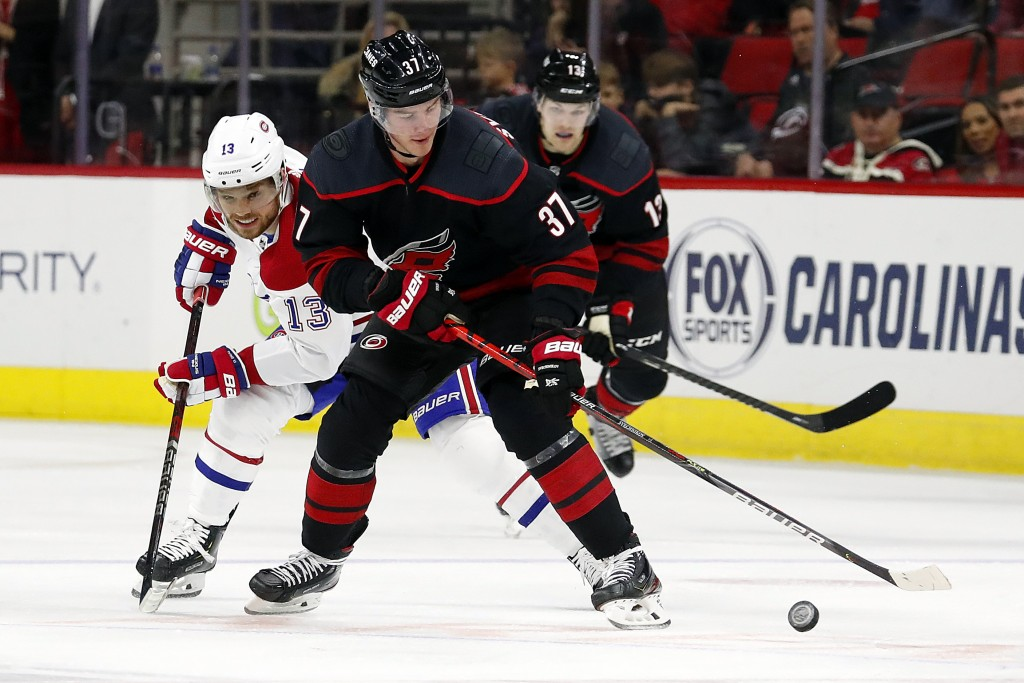 Carolina Hurricanes' Andrei Svechnikov (37), of Russia, protects the puck from Montreal Canadiens' Max Domi (13) during the second period of an NHL ho...