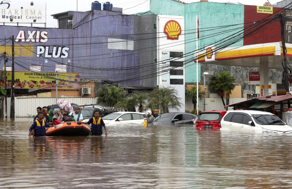 Indonesia rescue team evacuate residents from their flooded house at Jatibening on the outskirt of Jakarta, Indonesia, Wednesday, Jan. 1, 2020. Severe...
