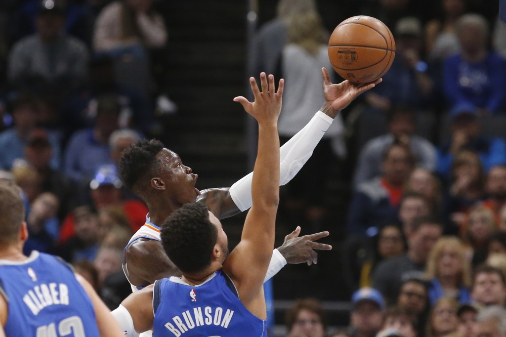 Oklahoma City Thunder guard Dennis Schroeder, rear, shoots in front of Dallas Mavericks guard Jalen Brunson during the first half of an NBA basketball...