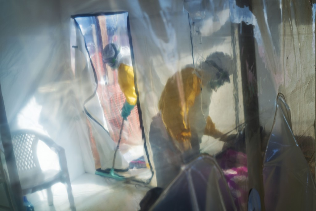 FILE - In this July 13, 2019 file photo, health workers wearing protective suits tend to an Ebola victim kept in an isolation cube in Beni, Congo. The...