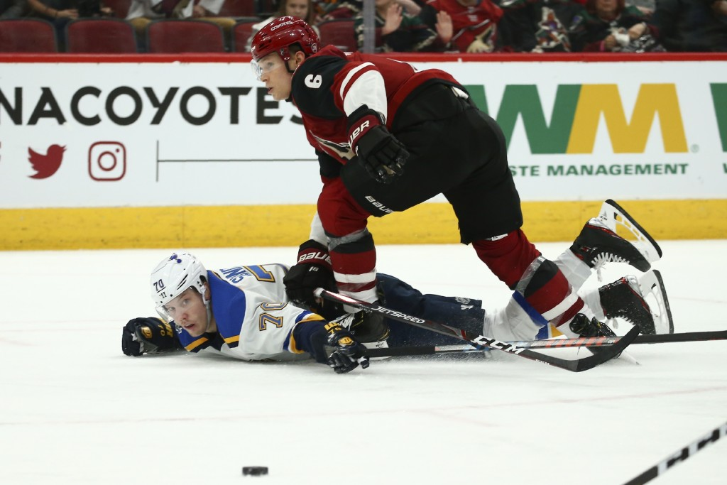 St. Louis Blues center Oskar Sundqvist (70) gets sent to the ice by Arizona Coyotes defenseman Jakob Chychrun (6) during the second period of an NHL h...