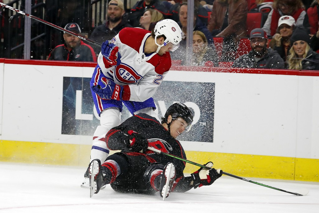 Montreal Canadiens' Ryan Poehling (25) collides with Carolina Hurricanes' Haydn Fleury (4) during the first period of an NHL hockey game in Raleigh, N...