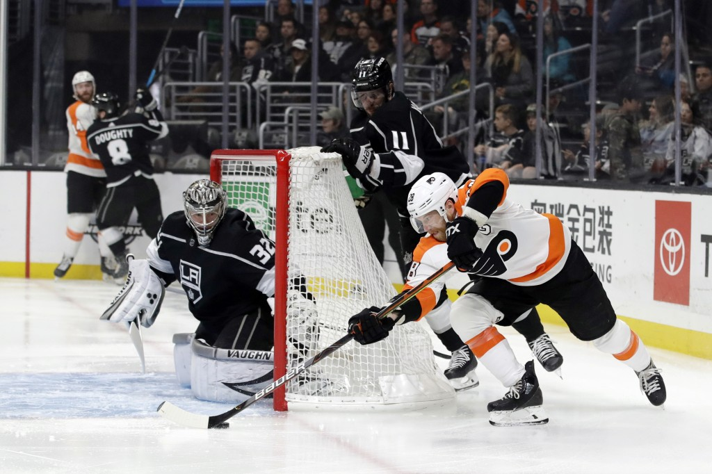 Philadelphia Flyers' Claude Giroux, right, tries to shoot past Los Angeles Kings goaltender Jonathan Quick during the first period of an NHL hockey ga...