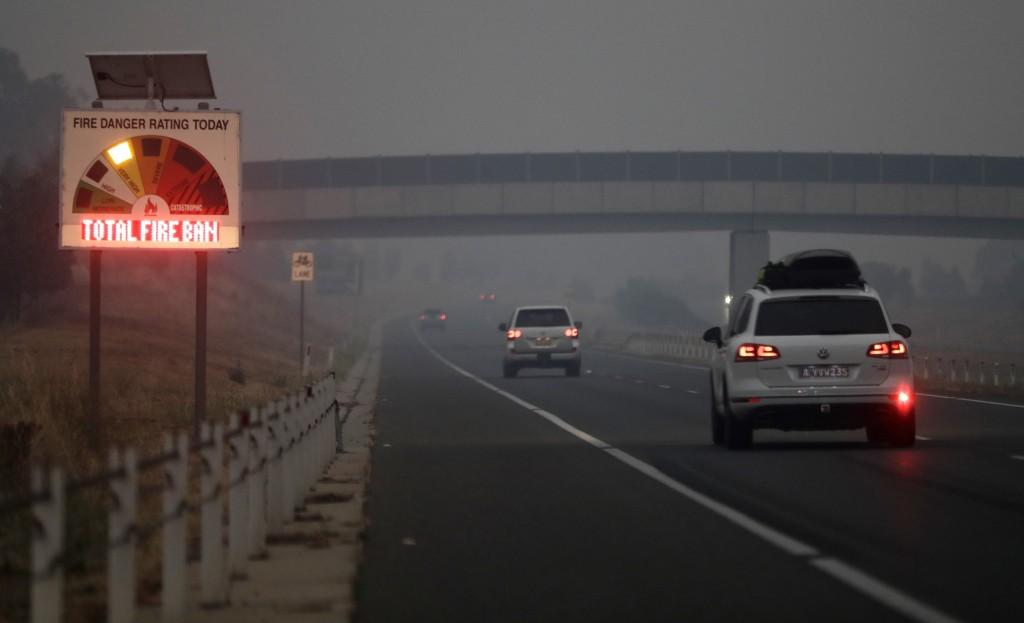 Cars drive down a freeway as smoke shrouds the Australian capital of Canberra, Australia, Wednesday, Jan. 1, 2020. Australia deployed military ships a...