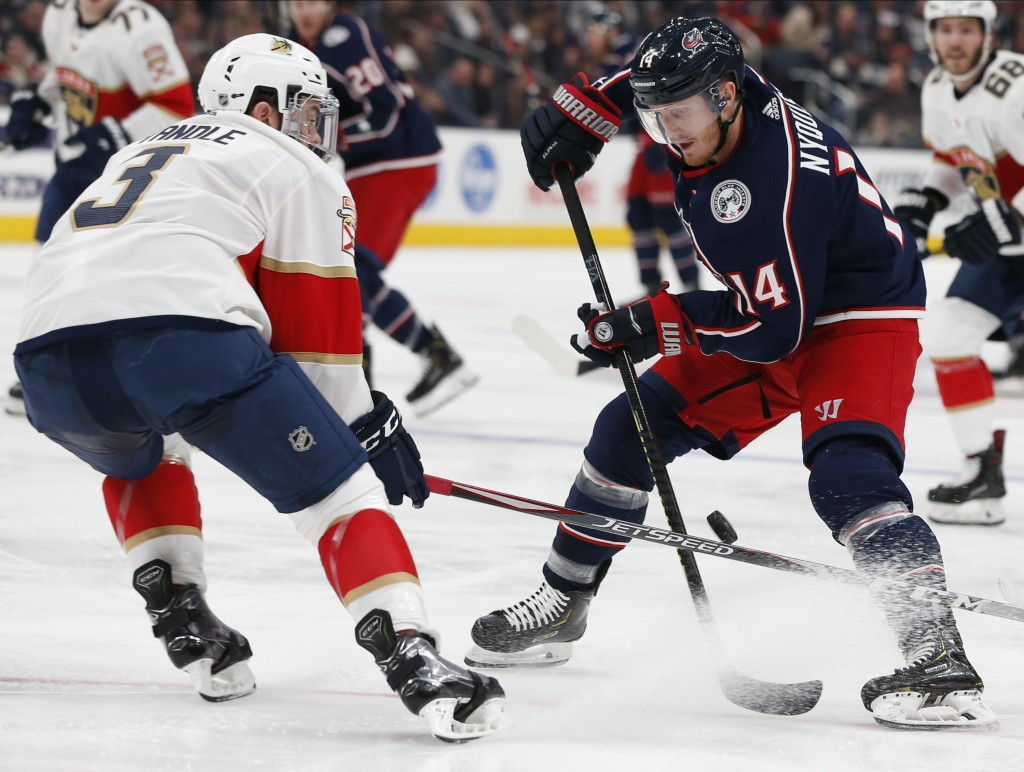 Columbus Blue Jackets' Gustav Nyquist, right, of Sweden, carries the puck up ice as Florida Panthers' Keith Yandle defends during the second period of...