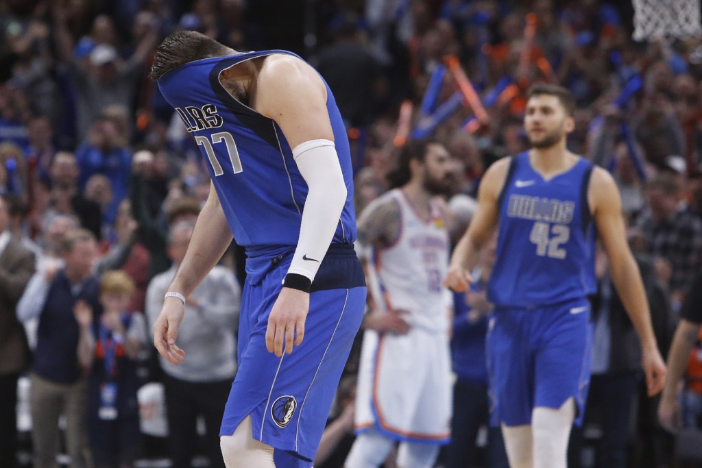 Dallas Mavericks forward Luka Doncic (77) pulls his jersey over his face after missing a shot late in the second half of the team's NBA basketball gam...