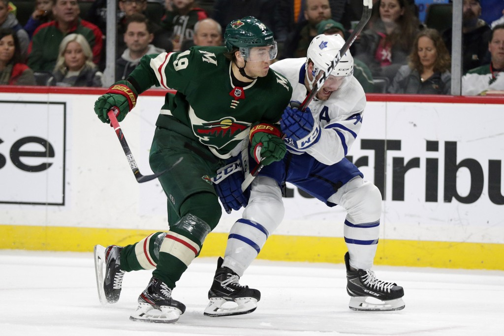 Minnesota Wild Luke Kunin (19) and Toronto Maple Leafs Morgan Rielly (44) vie for a puck in the first period of an NHL hockey game Tuesday, Dec. 31, 2...