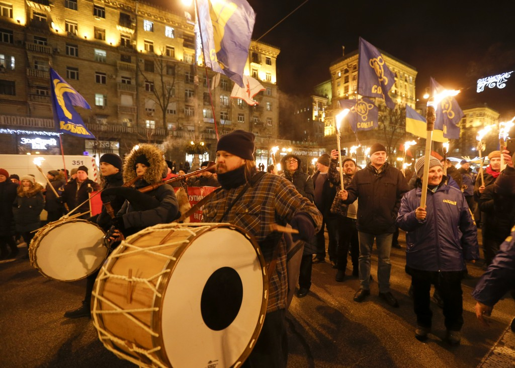 Activists of various nationalist parties play drums and carry torches during a rally in Kyiv, Ukraine, Wednesday, Jan. 1, 2020. The rally was organize...