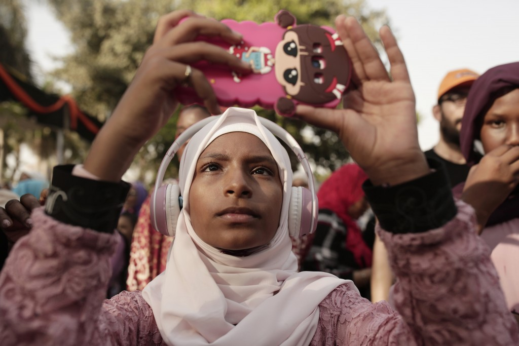 In this June 20, 2019 photo, a teenager films Sudanese dancers on her mobile phone during an event marking the U.N.'s International Refugee Day, in Ca...
