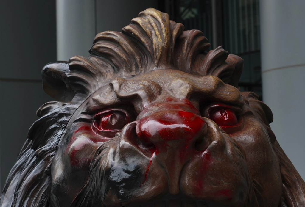 The lion statue in front of the international HSBC Bank branch is covered with red paint in Hong Kong, Thursday, Jan. 2, 2020. A huge crowd gathered i...
