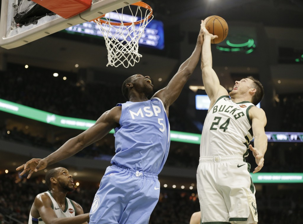 Milwaukee Bucks' Pat Connaughton, right and Minnesota Timberwolves' Gorgui Dieng reach for a rebound during the first half of an NBA basketball game W...