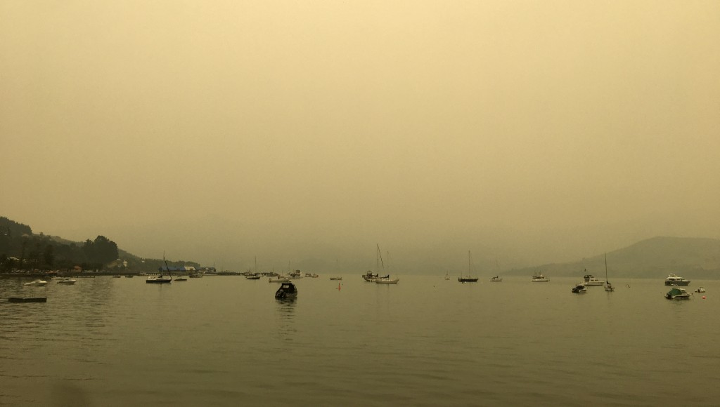 A yellow light illuminates the sky as the sun sets over Akaroa Harbor as smoke from the Australian wildfires arrives on the east coast of the South Is...