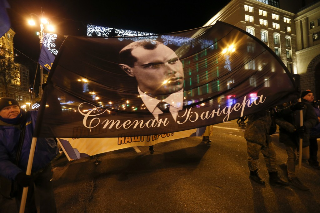 Activists of various nationalist parties carry torches and a portrait of Stepan Bandera during a rally in Kyiv, Ukraine, Wednesday, Jan. 1, 2020.  The...