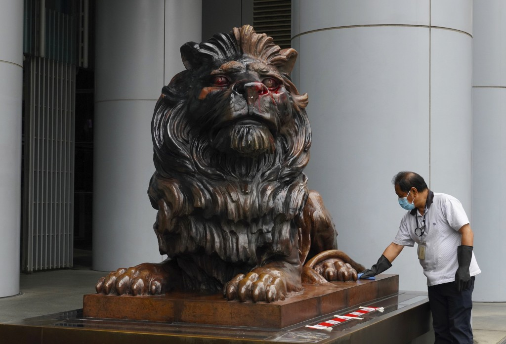 A worker cleans the iconic lion statue in front of the international HSBC Bank branch that was painted with red paint in Hong Kong, Thursday, Jan. 2, ...
