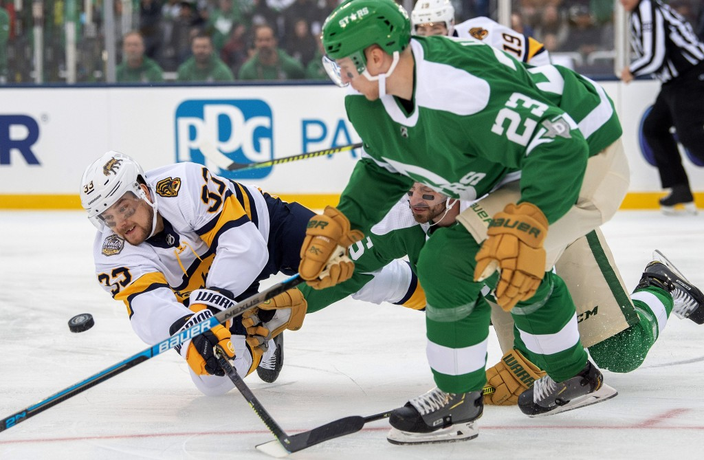 Nashville Predators right wing Viktor Arvidsson (33) dives to the ice as he competes for the puck with Dallas Stars defenseman Esa Lindell (23) and le...