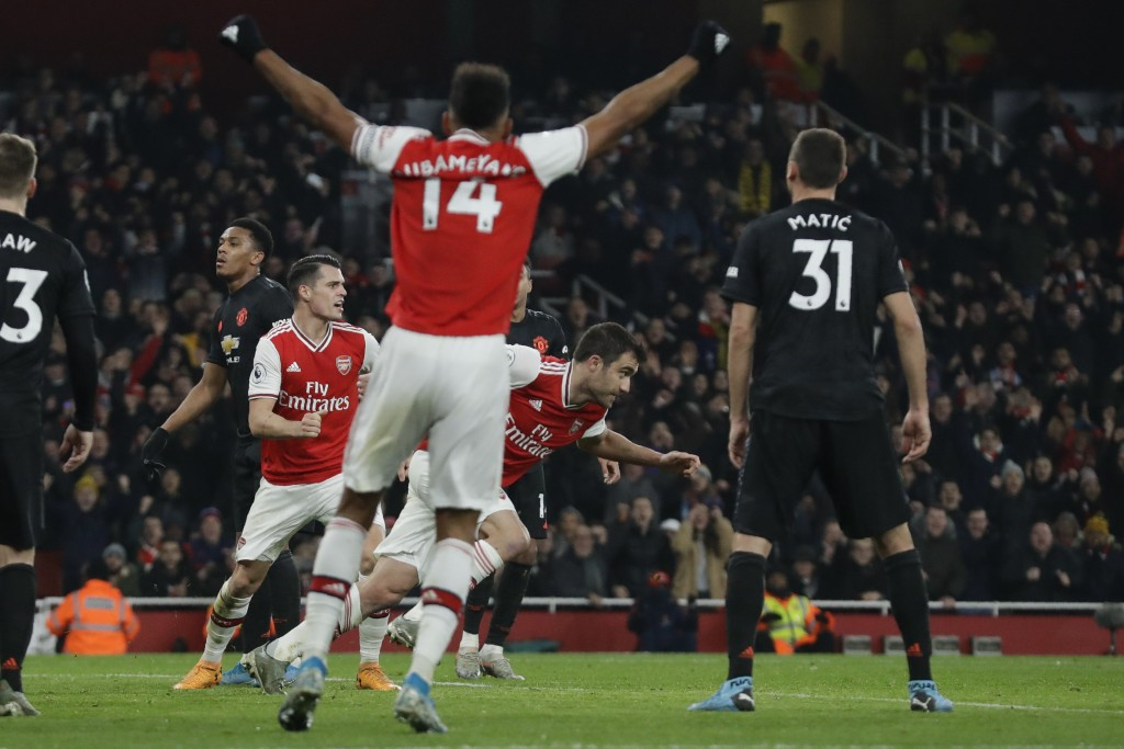 Arsenal's Sokratis Papastathopoulos, center, runs as he celebrates after scoring their side's second goal during the English Premier League soccer mat...