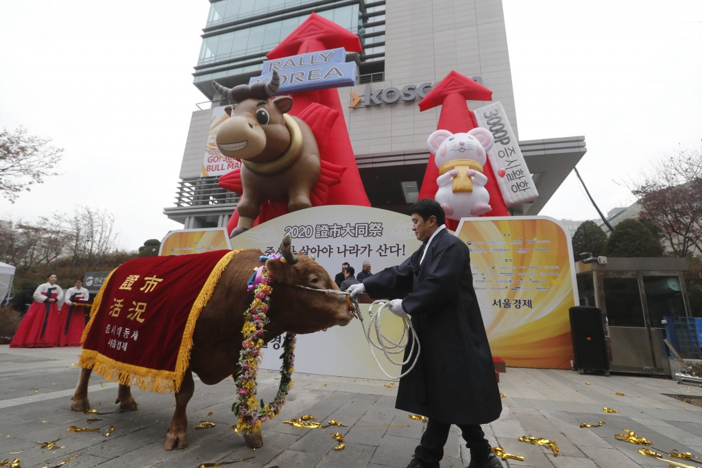A farmer parades with a bull to celebrate the opening of this year's trading in Seoul, South Korea, Thursday, Jan. 2, 2020. Asian shares were mostly h...
