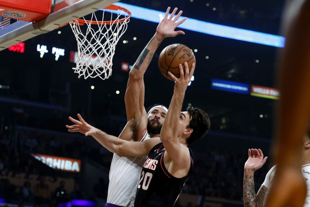 Phoenix Suns' Dario Saric (20) goes up to the basket under pressure from Los Angeles Lakers' JaVale McGee during the first half of an NBA basketball g...
