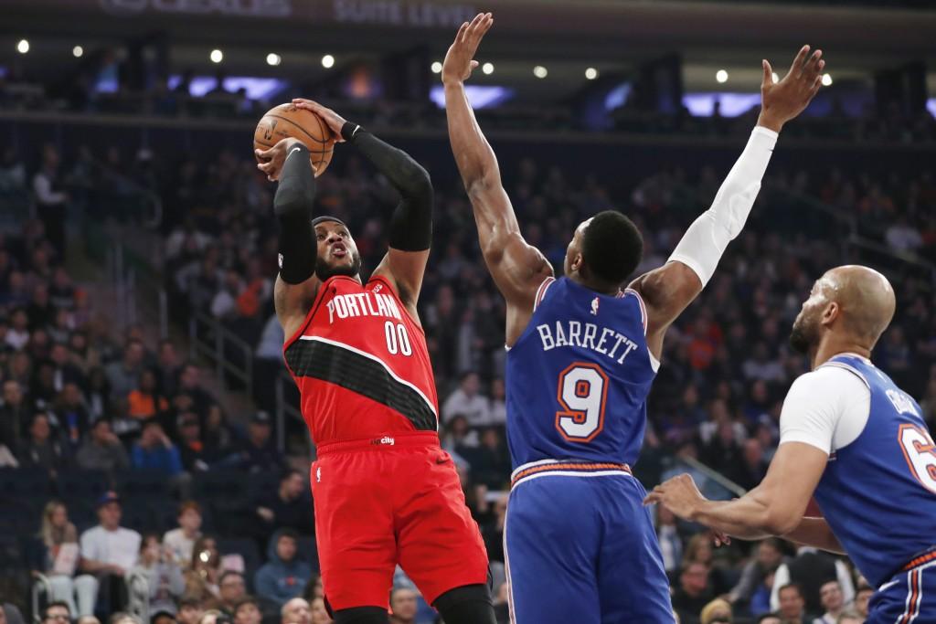 New York Knicks guard RJ Barrett (9) defends as Portland Trail Blazers forward Carmelo Anthony (00) shoots during the first half of an NBA basketball ...