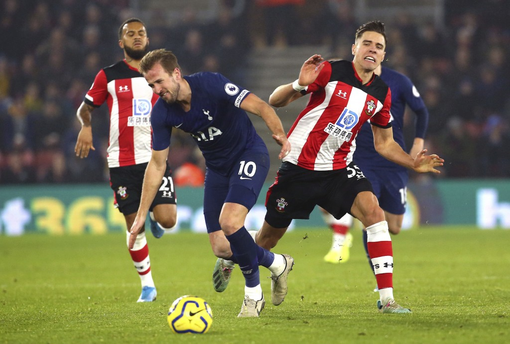 Tottenham Hotspur's Harry Kane, left and Southampton's Jan Bednarek battle for the ball, during the English Premier League soccer match between Southa...