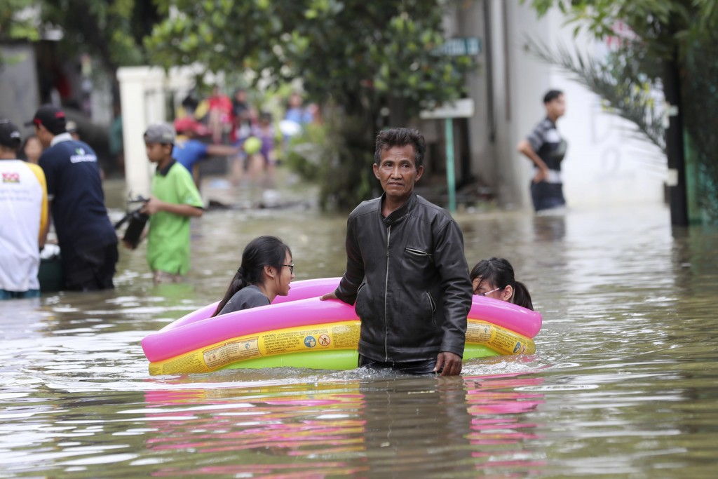Residents wade through a flooded neighborhood in Tanggerang on the outskirts of Jakarta, Indonesia, Thursday, Jan. 2, 2020. Severe flooding in Indones...