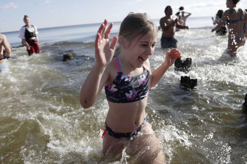 A girl reacts while hurrying out of the Chesapeake Bay after dipping in the frigid waters as part of a polar bear plunge New Year event, Wednesday, Ja...