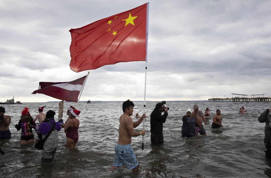 A swimmer carries the Chinese flag during the annual New Year's Day Coney Island Polar Bear Plunge, Wednesday, Jan. 1, 2020 in the Brooklyn borough of...