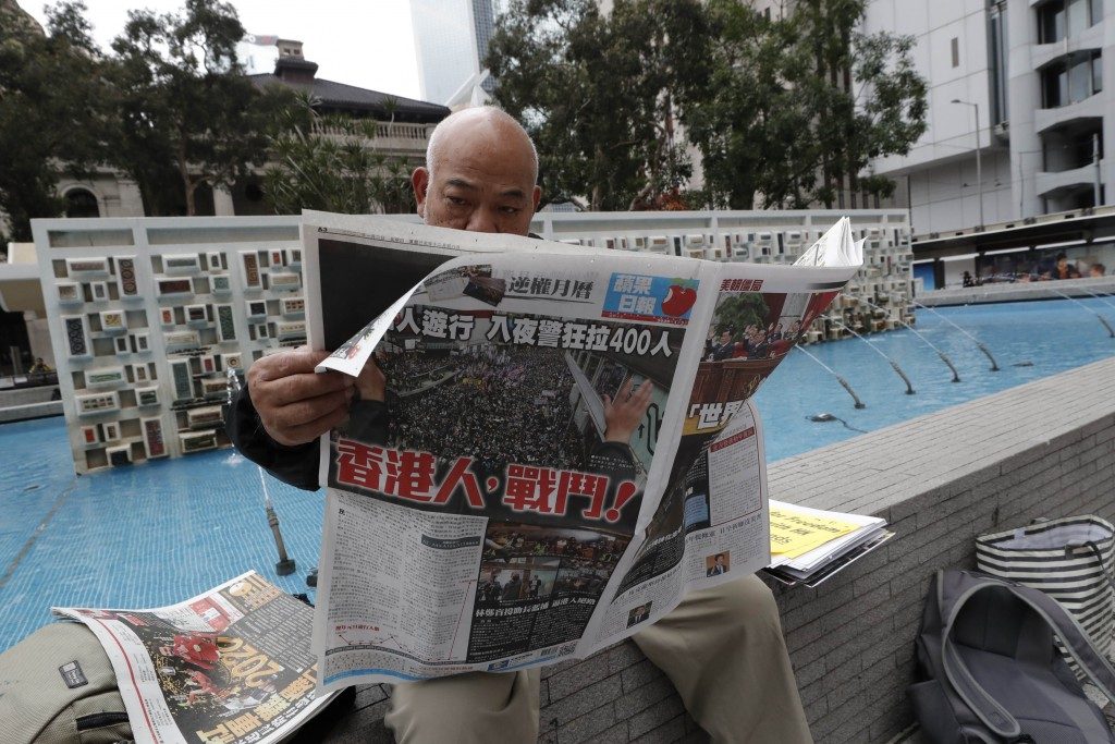 """A man reads a newspaper reporting New Year's Day protest with the headline """"Hong Kongers, Fight!"""" in Hong Kong, Thursday, Jan. 2, 2020. Hundreds of th..."""