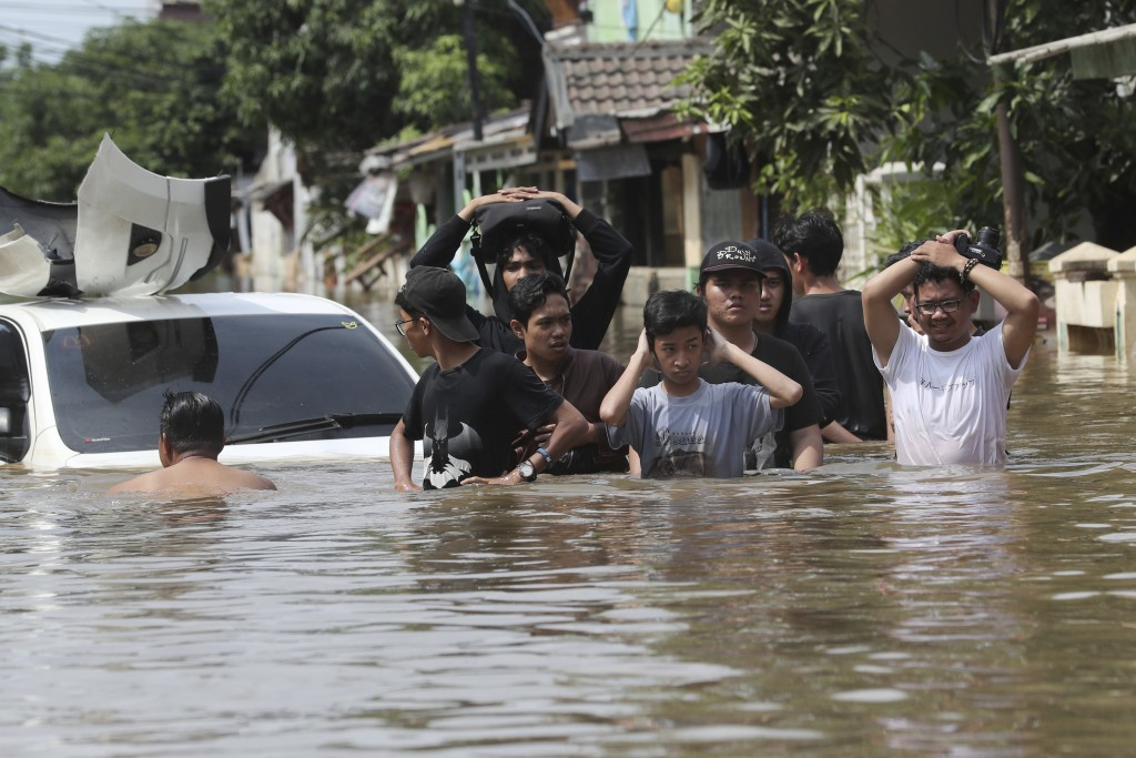 People walk through a flooded neighborhood in Tanggerang, outisde Jakarta, Indonesia, Thursday, Jan. 2, 2020. Heavy flooding in Indonesia's capital as...
