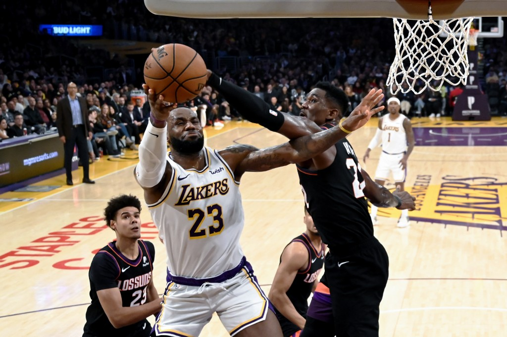Los Angeles Lakers' LeBron James (23) goes up to basket under pressure from Phoenix Suns' Deandre Ayton (22) during the second half of an NBA basketba...
