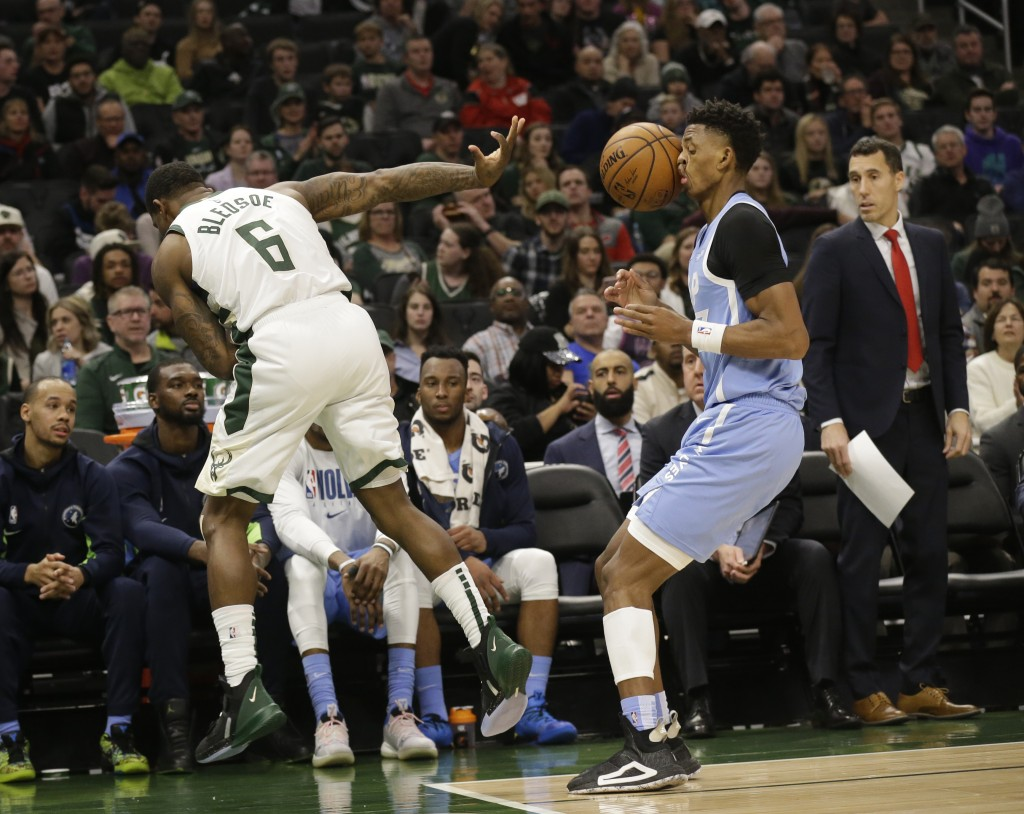 Milwaukee Bucks' Eric Bledsoe (6) throws the ball off the face of Minnesota Timberwolves' Jarrett Culver and the ball goes out of bounds awarded to Mi...