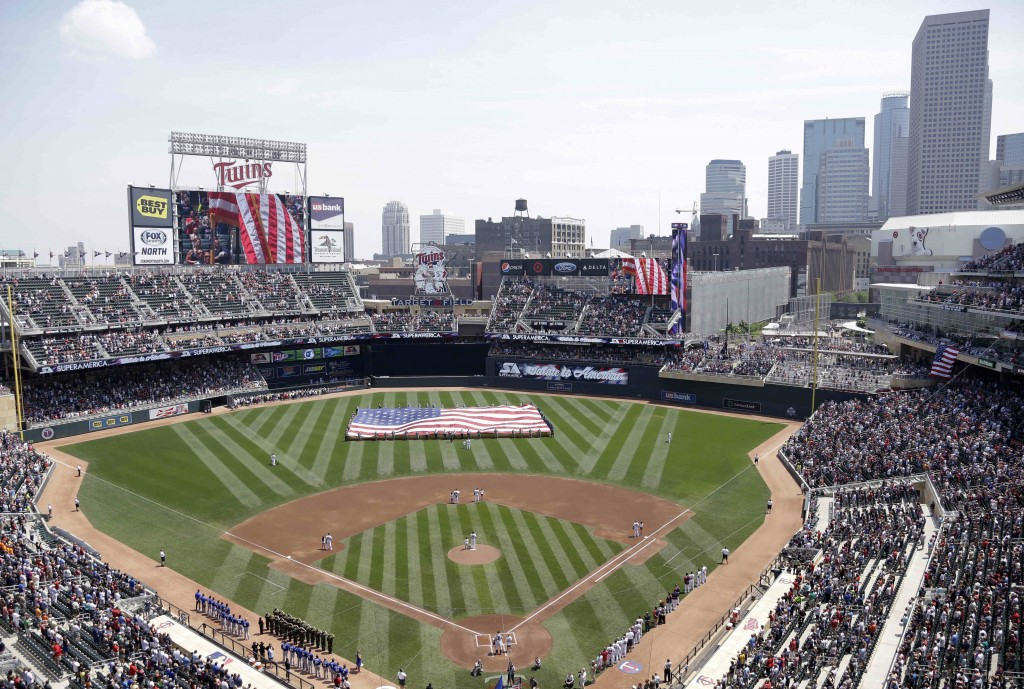 FILE - In this June 30, 2013 file photo, members of the Armed Forces hold a large flag at Target field in Minneapolis where the Minnesota Twins hosted...