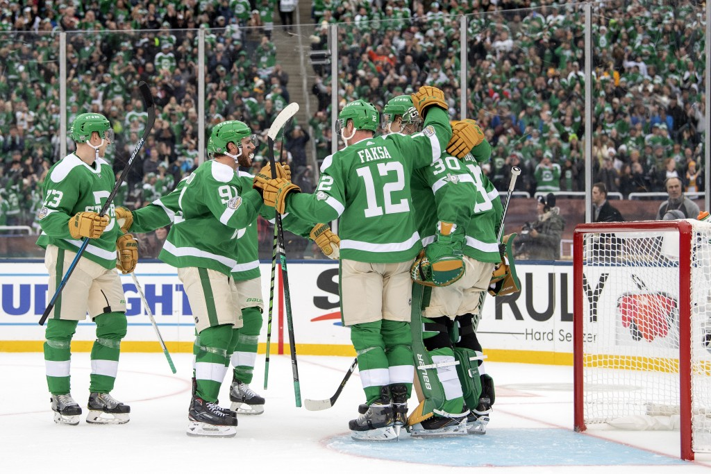 The Dallas Stars celebrate their 4-2 win over the Nashville Predators at the end of the NHL Winter Classic hockey game at the Cotton Bowl, Wednesday, ...