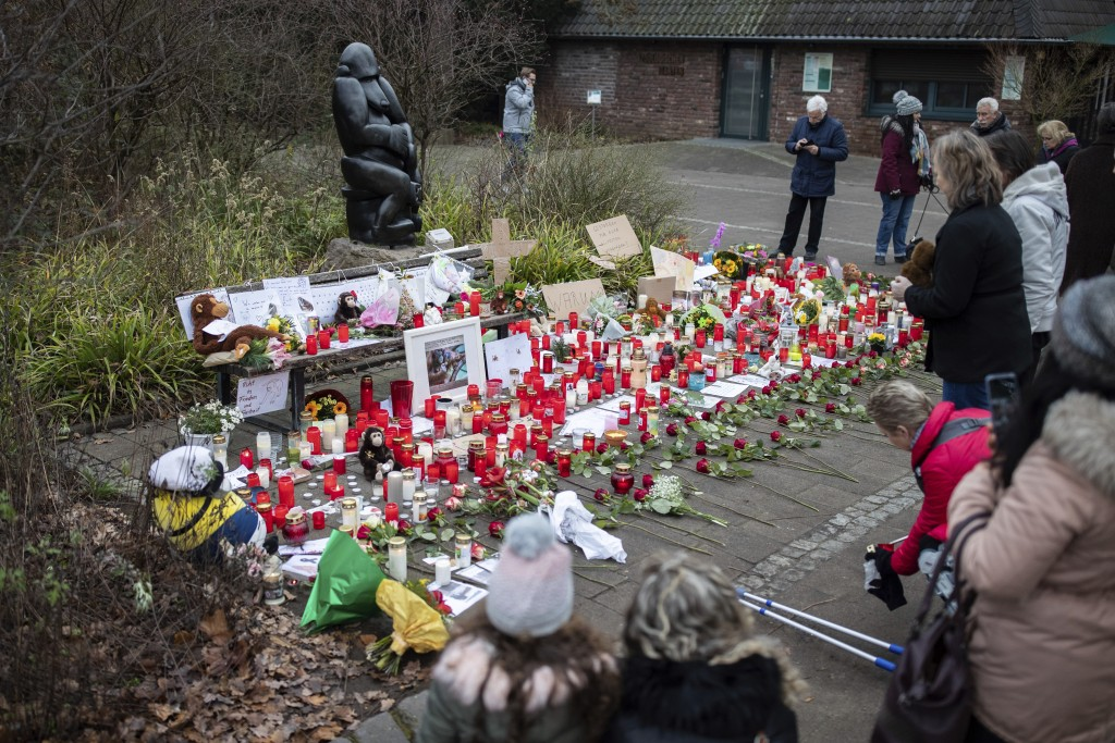 A women lights a candle at the main entrance of the Zoo in Krefeld, Germany, Thursday, Jan. 2, 2020. Three woman are under investigation for launching...
