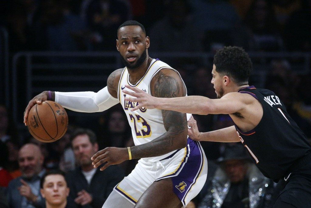 Los Angeles Lakers' LeBron James (23) is defended by Phoenix Suns' Devin Booker (1) during the first half of an NBA basketball game Wednesday, Jan. 1,...
