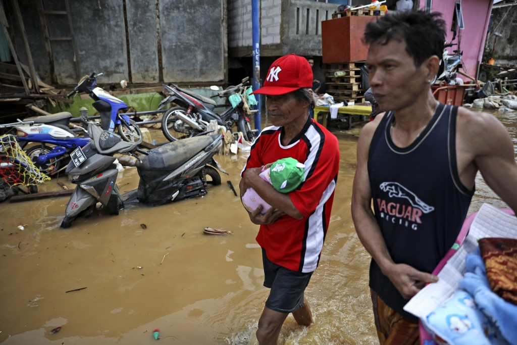 A man carries his baby niece through a flooded neighborhood in Jakarta, Indonesia, Thursday, Jan. 2, 2020. Severe flooding in the capital as residents...