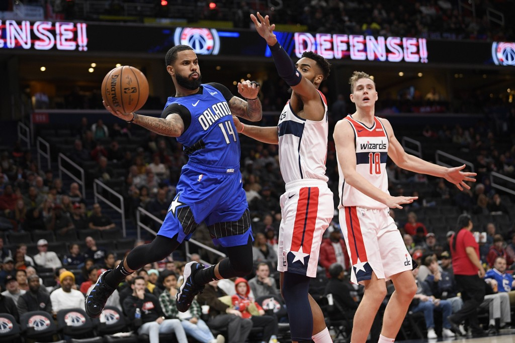 Orlando Magic guard D.J. Augustin (14) looks to pass the ball next to Washington Wizards guard Troy Brown Jr., center, and center Anzejs Pasecniks (18...