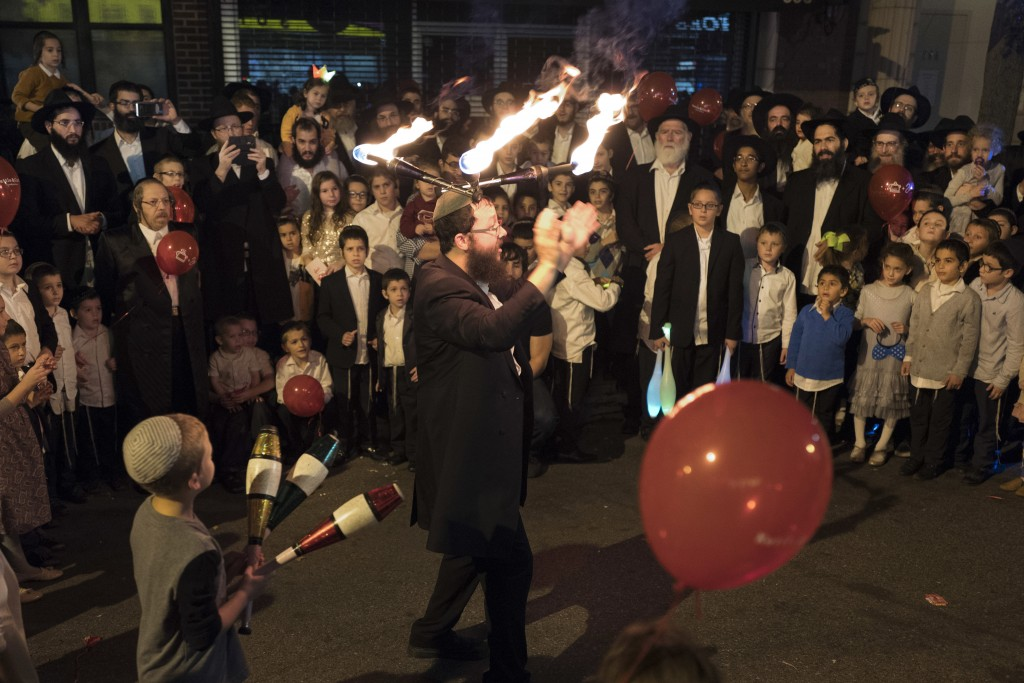 FILE - In this Oct. 18, 2016, file photo, a performer wears lighted sticks on his head while entertaining a crowd during the Jewish holiday of Sukkot,...