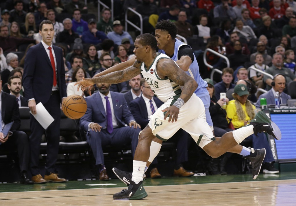 Milwaukee Bucks' Eric Bledsoe, front, and Minnesota Timberwolves' Jarrett Culver chase down a loose ball during the first half of an NBA basketball ga...