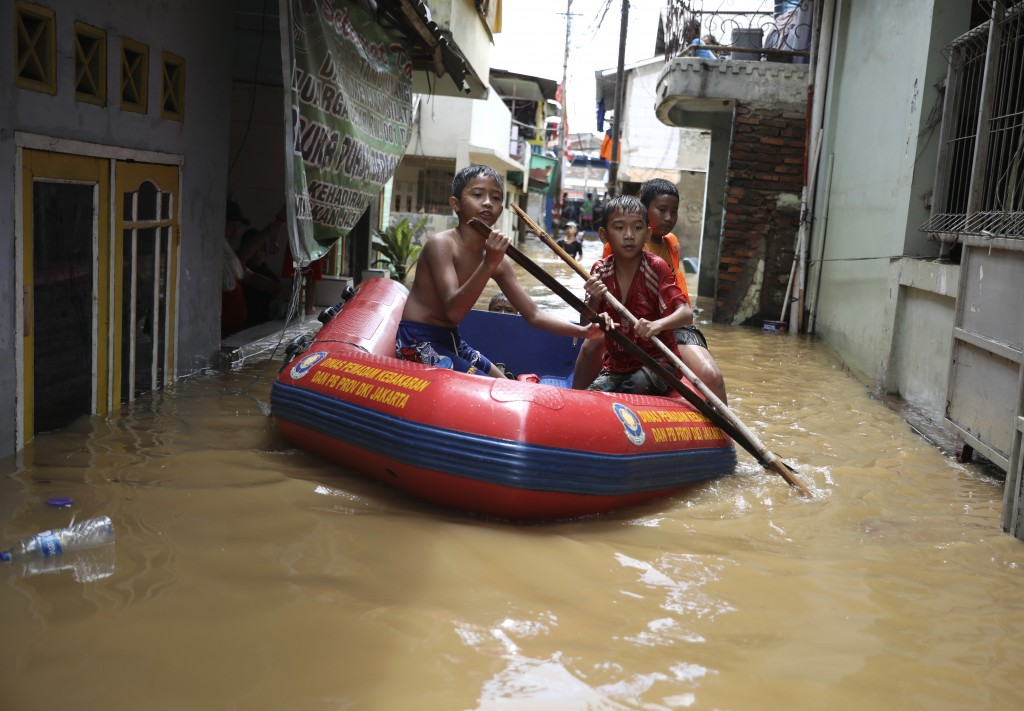 Youths use an inflatable raft to move through a flooded neighborhood in Jakarta, Indonesia, Thursday, Jan. 2, 2020. Severe flooding in the capital as ...