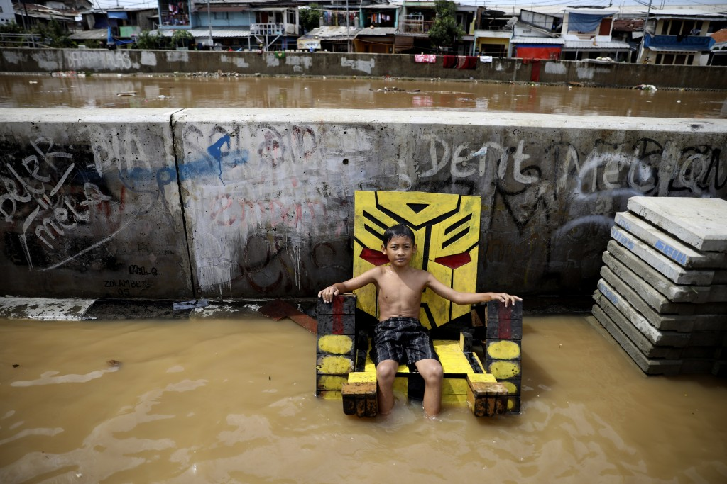 A young boy sits on a chair in a flooded neighborhood in Jakarta, Indonesia, Thursday, Jan. 2, 2020. Severe flooding in the capital as residents celeb...