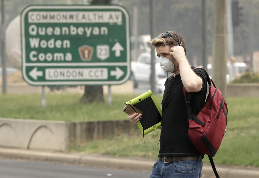 A pedestrian wears a mask as smoke shrouds the Australian capital of Canberra, Australia, Thursday, Jan. 2, 2020. Australia deployed military ships an...