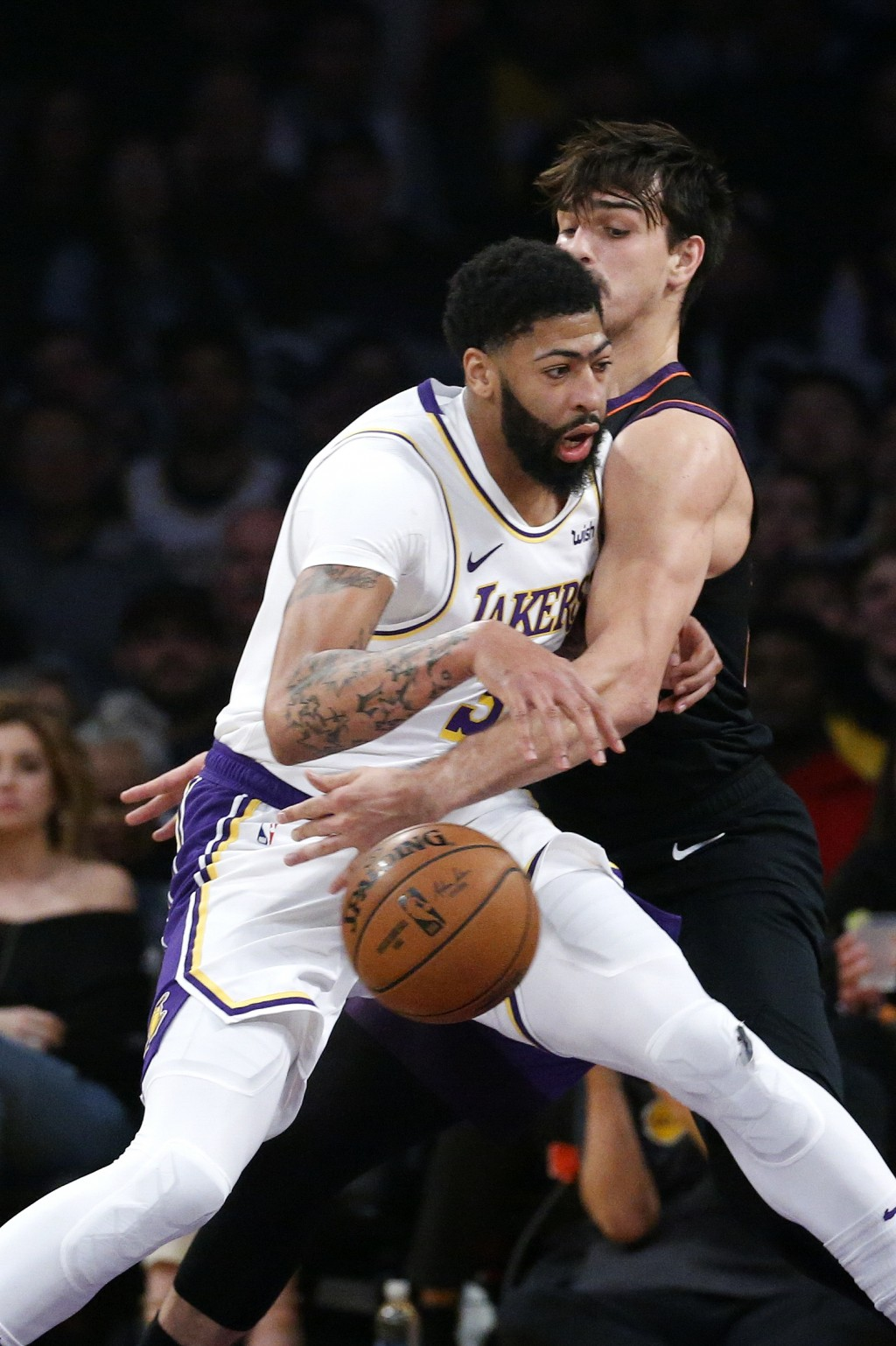 Los Angeles Lakers' Anthony Davis, left, is defended by Phoenix Suns' Dario Saric during the first half of an NBA basketball game Wednesday, Jan. 1, 2...