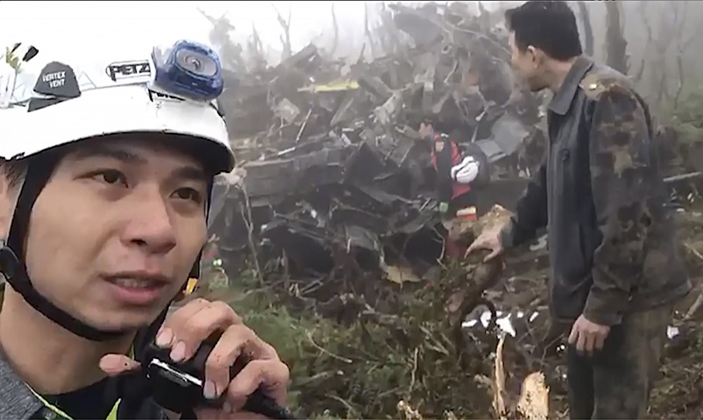 In this image made from video, emergency teams work at the crash site of a military helicopter in the mountains of Yilan, north eastern Taiwan, Thursd...