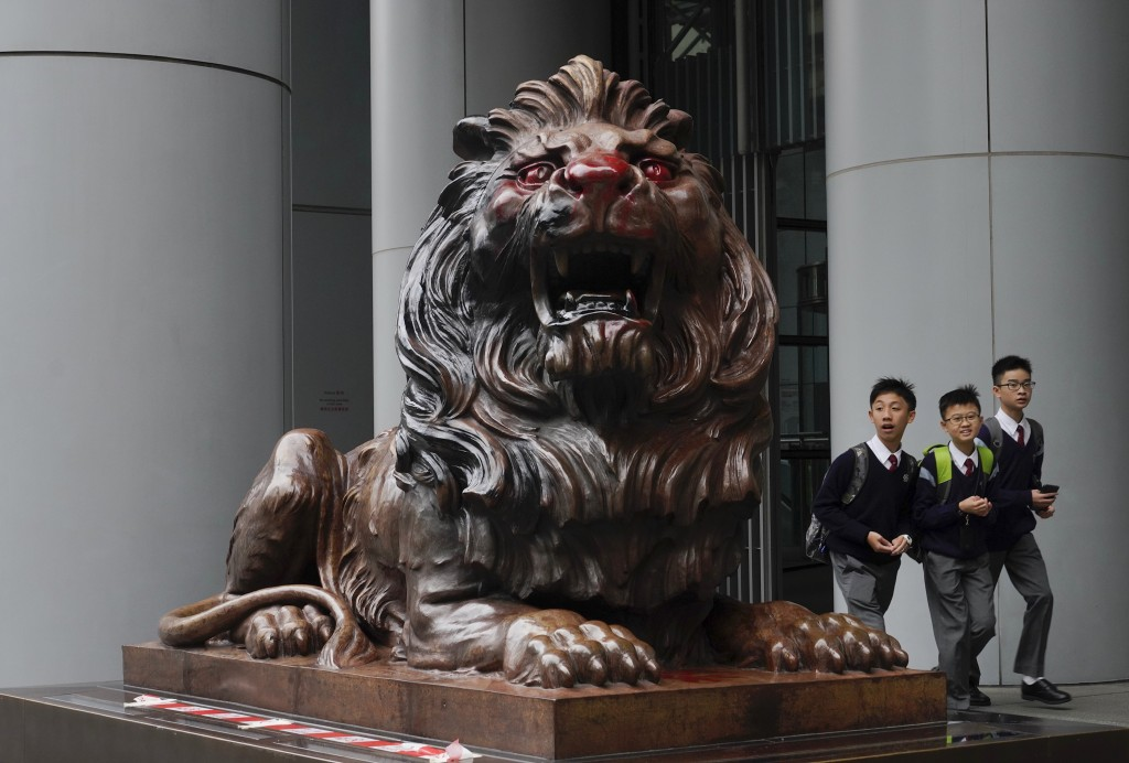 Students walks next to the iconic lion statue in front of the international HSBC Bank branch that was painted with red paint in Hong Kong, Thursday, J...