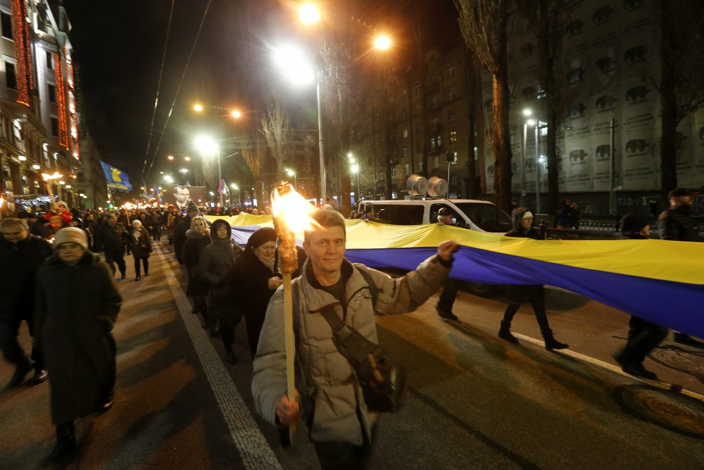 Activists of various nationalist parties carry flag and torches during a rally in Kyiv, Ukraine, Wednesday, Jan. 1, 2020. The rally was organized to m...