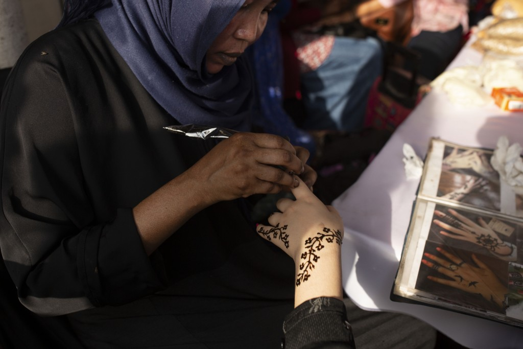 In this June 20, 2019 photo, a Sudanese woman applies henna to a Yemeni girl's hand during an event marking the U.N.'s International Refugee Day, in C...