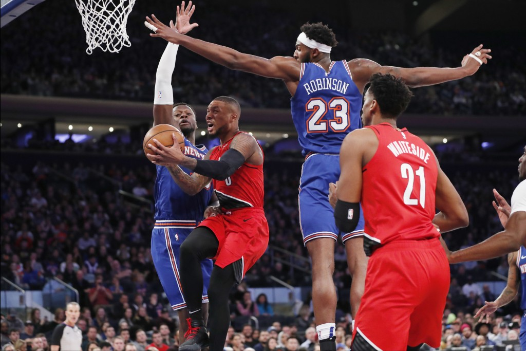 Portland Trail Blazers' Damian Lillard goes to the basket as New York Knicks forward Julius Randle, left, and center Mitchell Robinson (23) defend and...